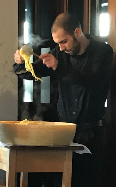 The chef is mixing the noodles with cheese.